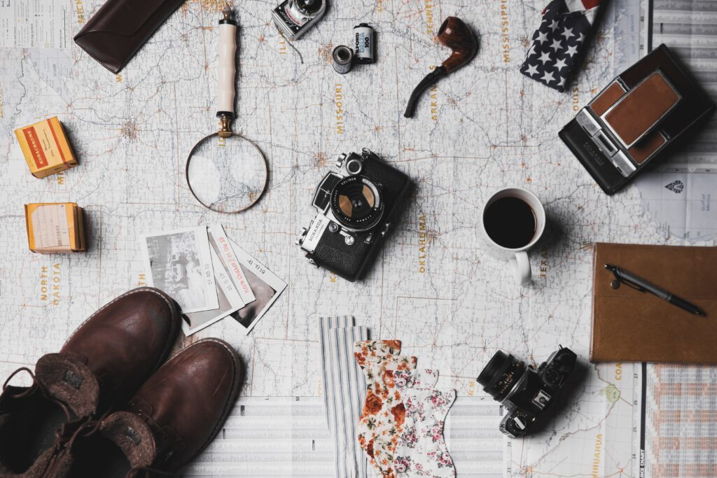 Map with a number of travel items, including a camera, coffee, pipe, magnifying glass, shoes, etc.