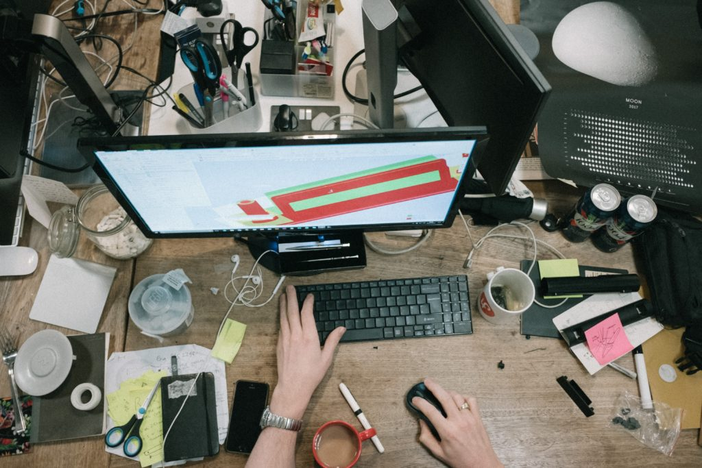 a cluttered desk with a person working