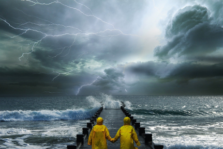 Two people in raincoats hold hands and look out at a storm at sea