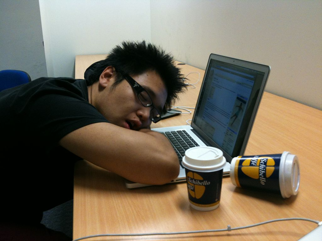 Man sleeping on his computer with two disposable coffee cups beside him