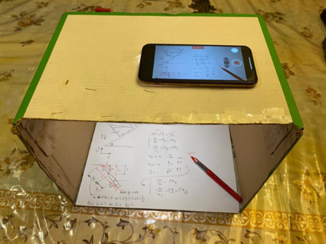 A cardboard box standing, with a phone laying on the top, the camera viewing downward through a hole to a paper and pencil.