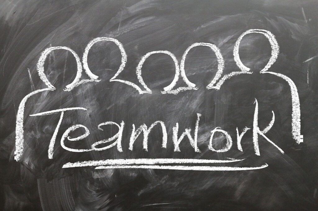 Chalkboard drawing with a team of people and the word Teamwork underlined