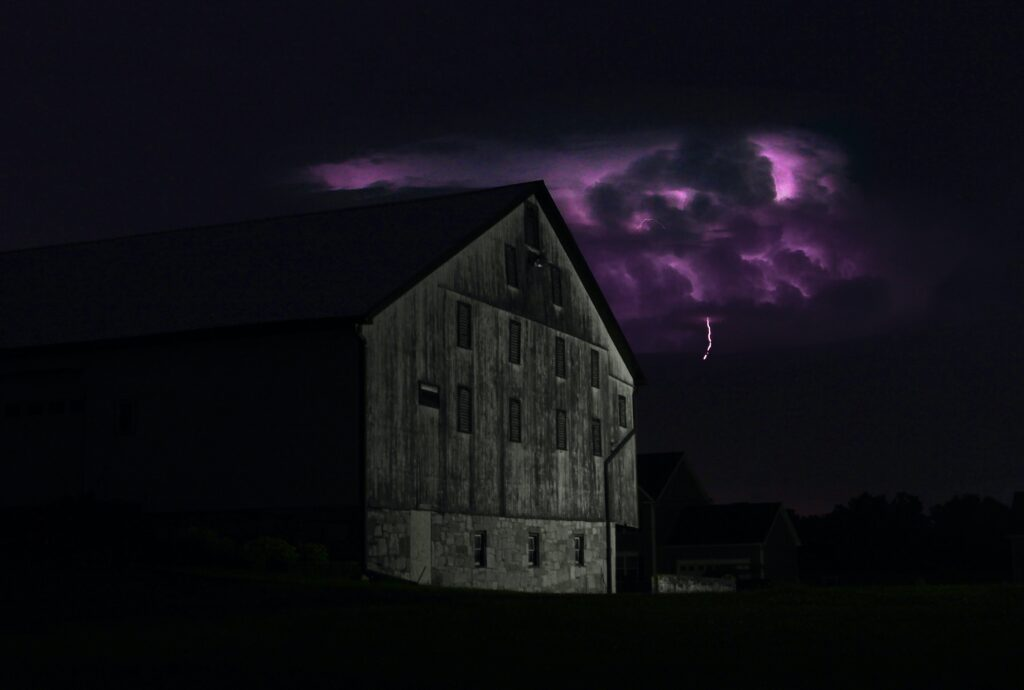 A dark sky at night with clouds lit up by a lightning storm, behind a large, dark barn in the foreground that is lit up slightly by the storm, together conveying a mood of mystery and suspense.