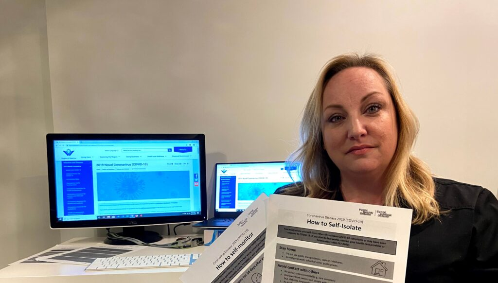 Amber Anderson-Lunn holding a document, How to Self-Isolate, with two active computer monitors behind her