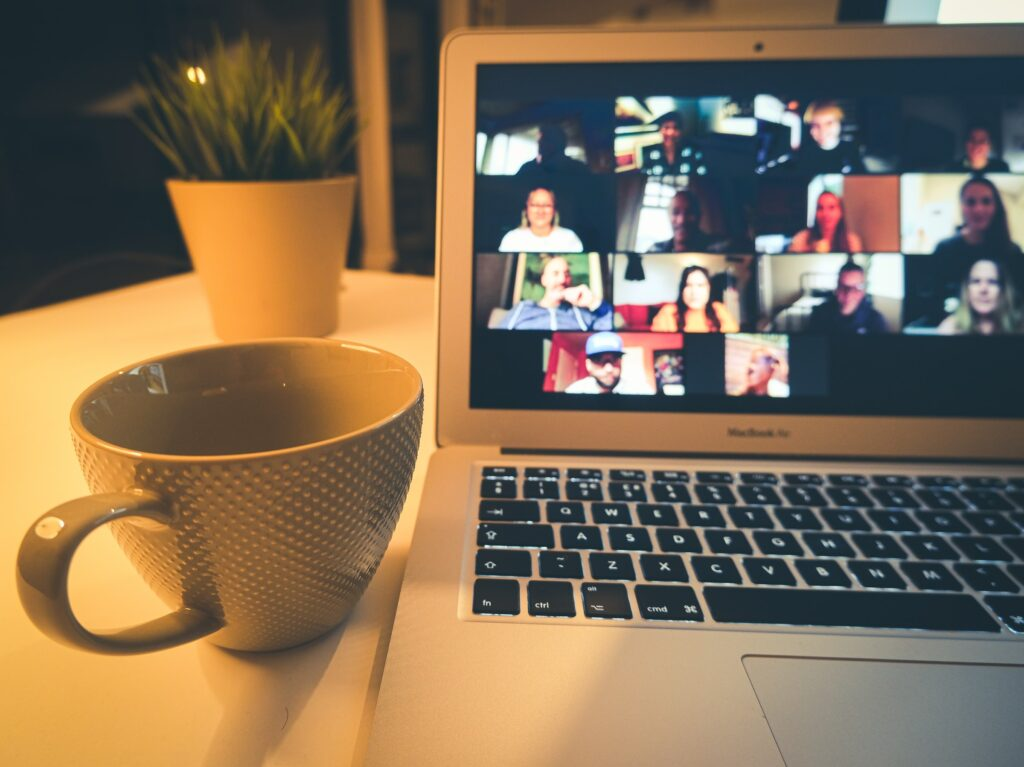 A person is sitting at their desk attending a class via Zoom. They have a cup sitting to the left of their laptop computer.