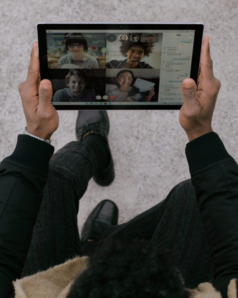 A person is holding a tablet and attending a class meeting via Zoom. They are interacting with four of their classmates and chatting with each other.